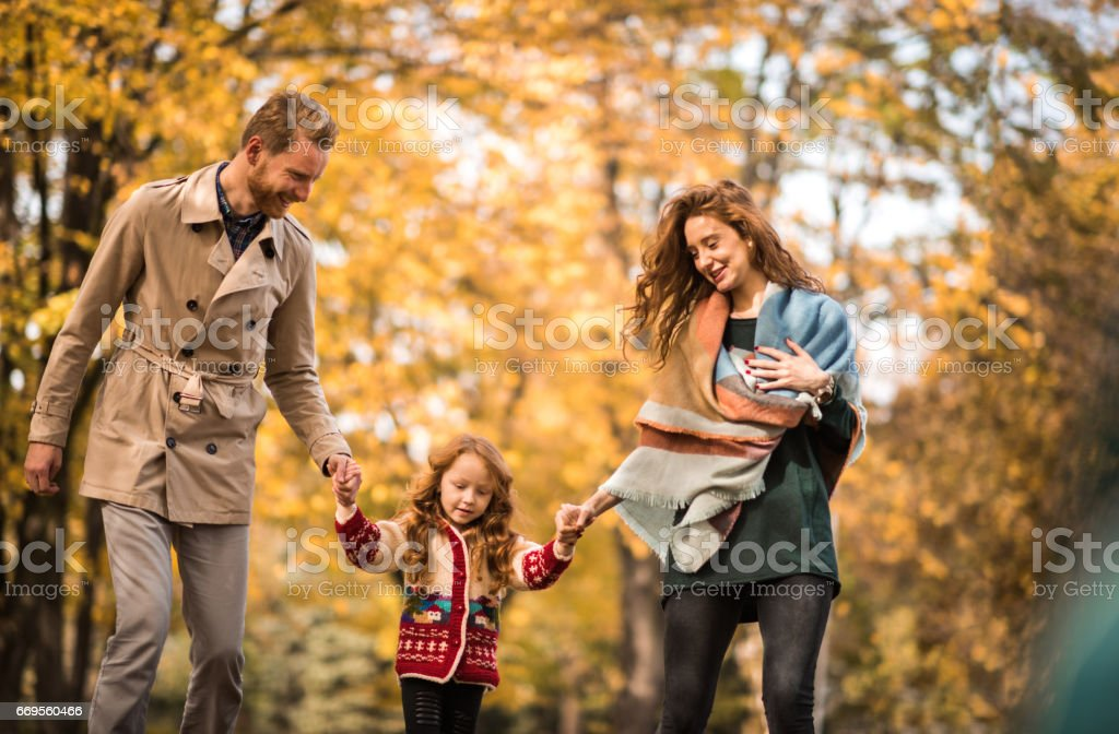 Young happy parents holding hands with their small daughter while...