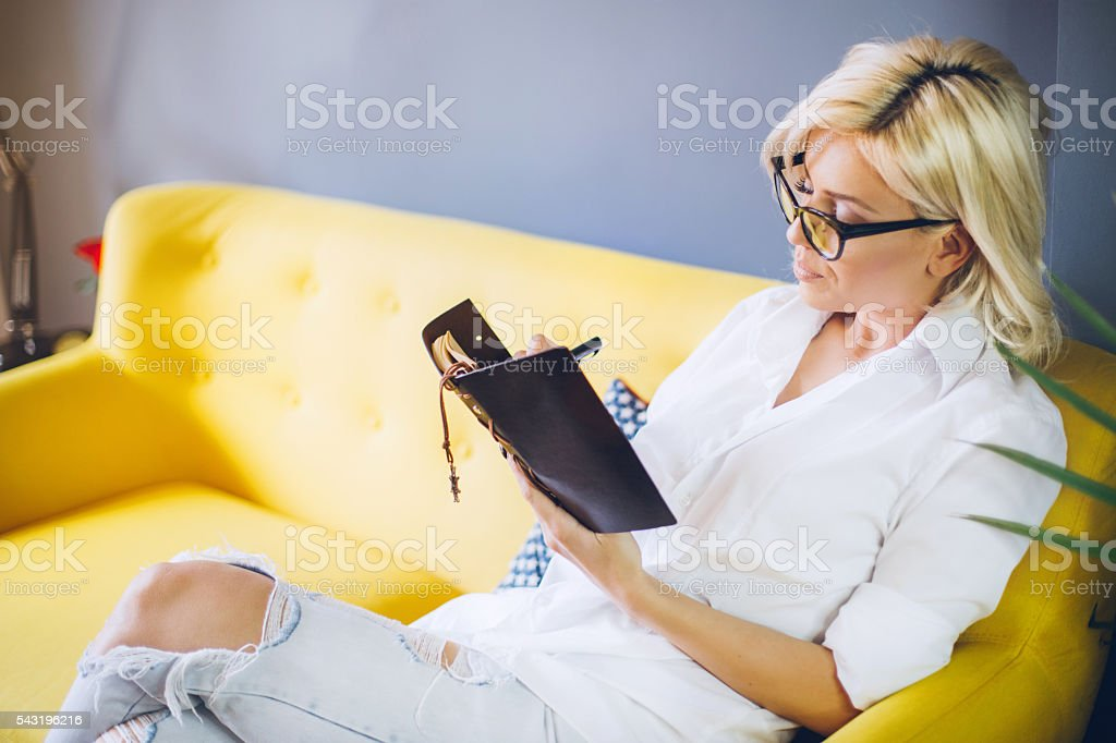 Happy relaxed blonde woman writing in her diary stock photo