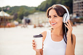 happy relaxed woman listening music in headphones and drinking coffee