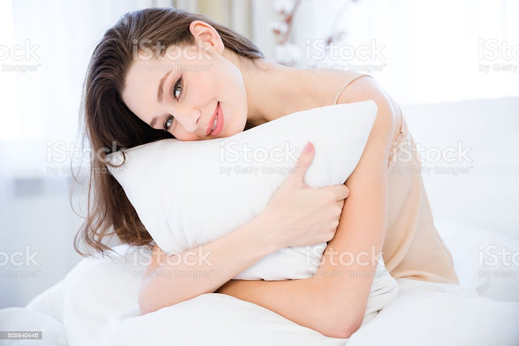Happy relaxed young woman hugging pillow on bed stock photo