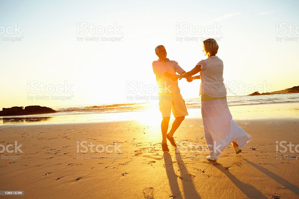 Happy retired couple enjoying together on beach royalty-free stock photo