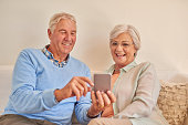 Happy retired couple looking at smart phone at phone