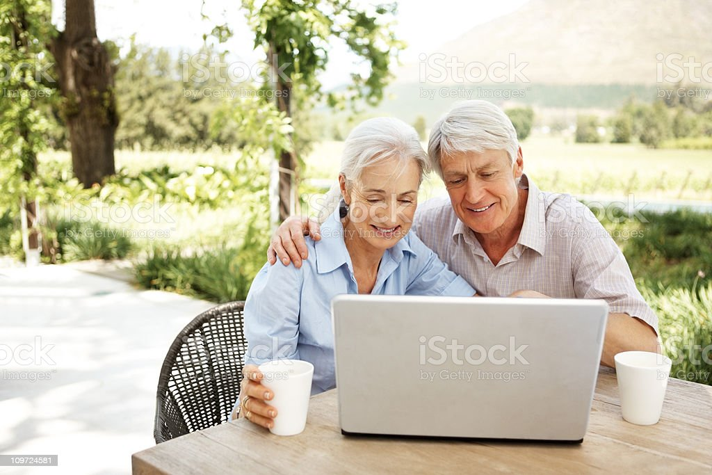 Happy retired couple using a laptop outdoors royalty-free stock photo