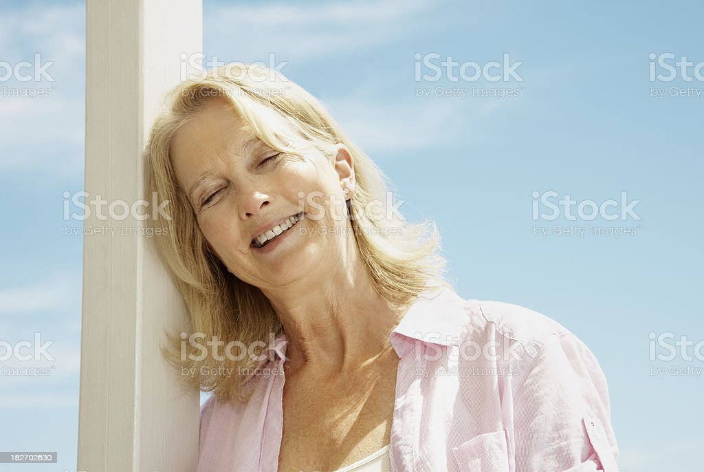 Happy retired woman against the clear blue sky royalty-free stock photo