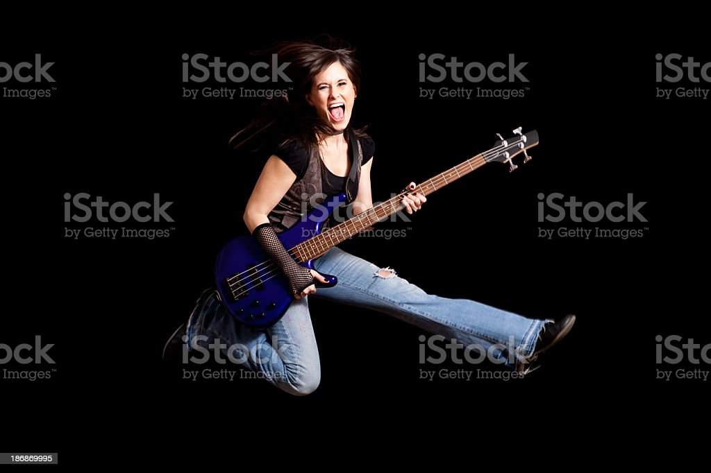 Happy Rocker Girl Jumping with Bass Guitar on Black Background royalty-free stock photo