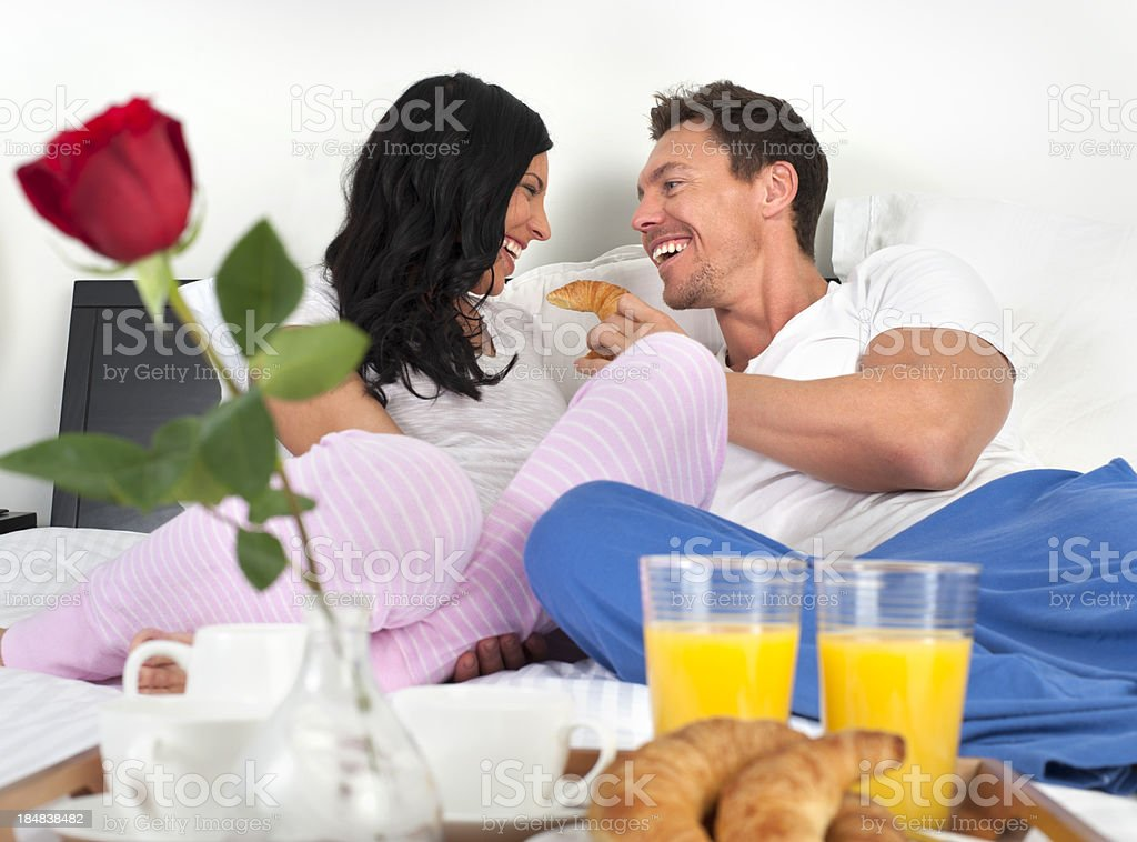 Happy romantic couple eating breakfast in bed royalty-free stock photo