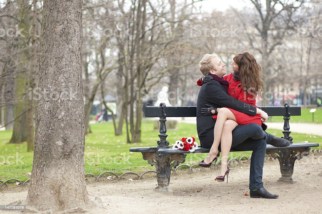 Happy romantic couple hugging on a bench royalty-free stock photo