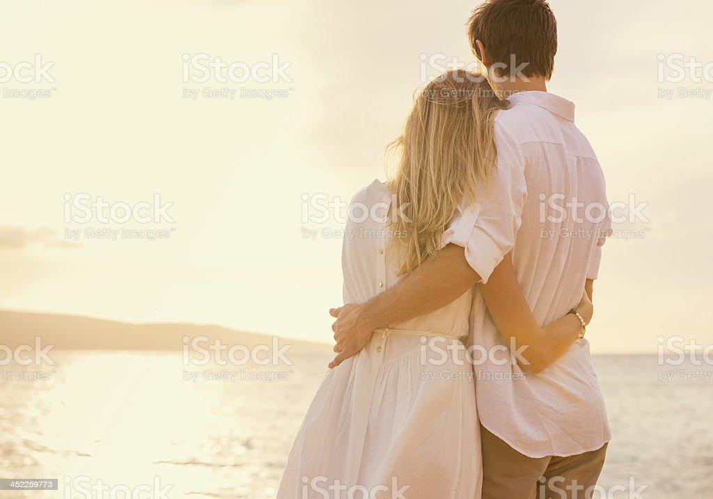 Happy romantic couple on the beach at sunset stock photo