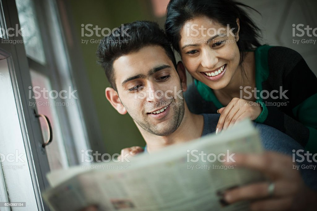 Happy romantic couple reading newspaper together. stock photo