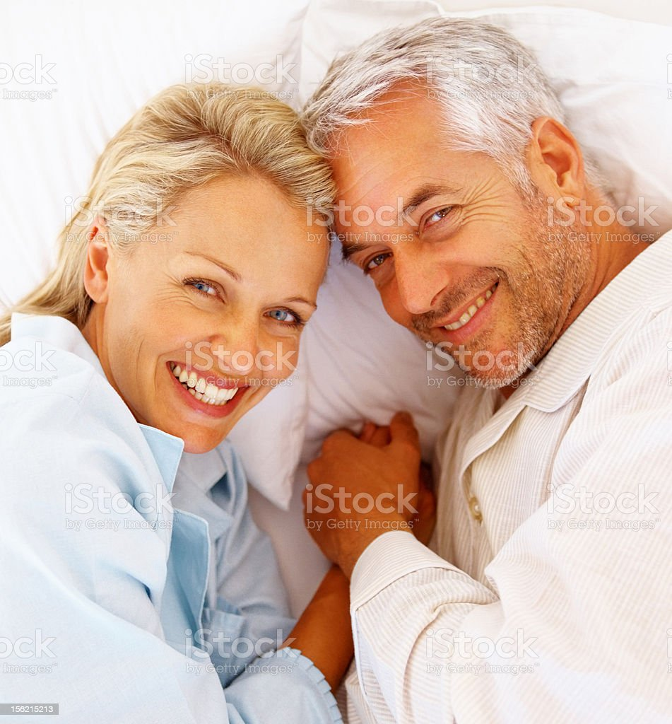 Happy romantic mature couple lying on bed royalty-free stock photo