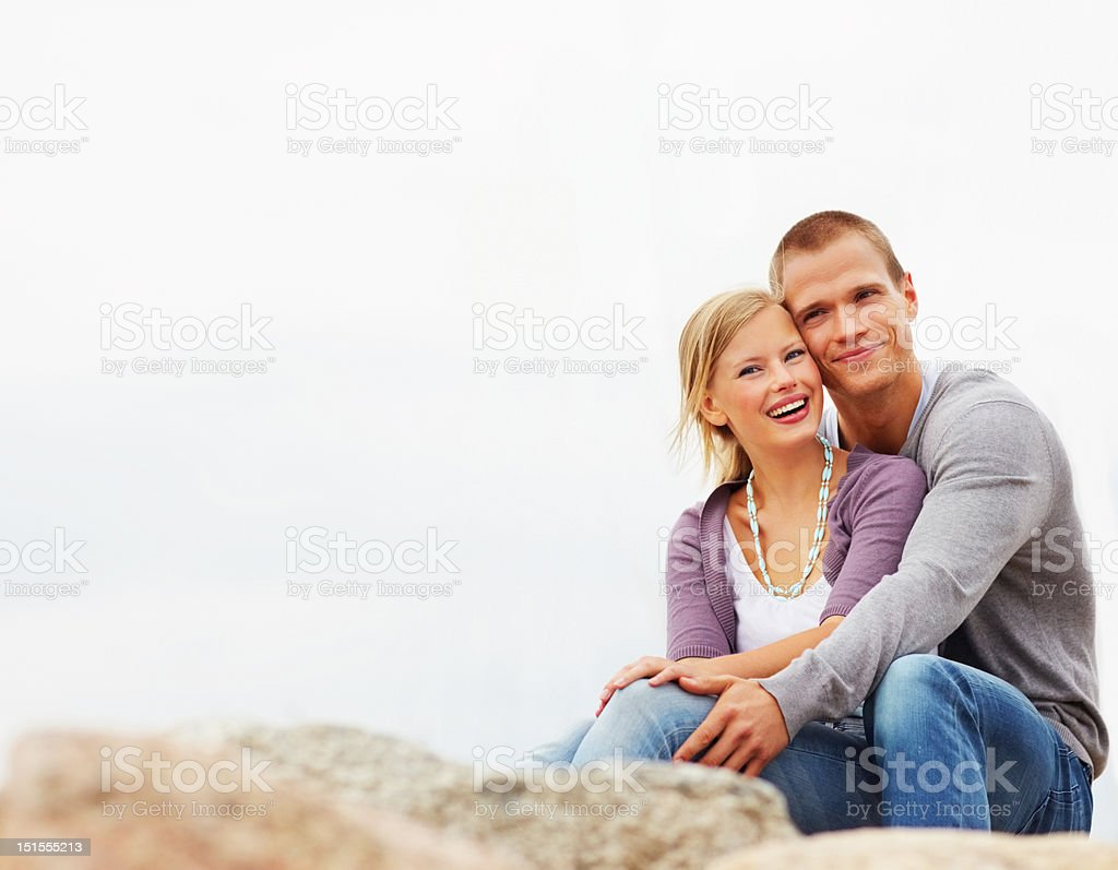 Happy romantic young couple sitting on rocks royalty-free stock photo