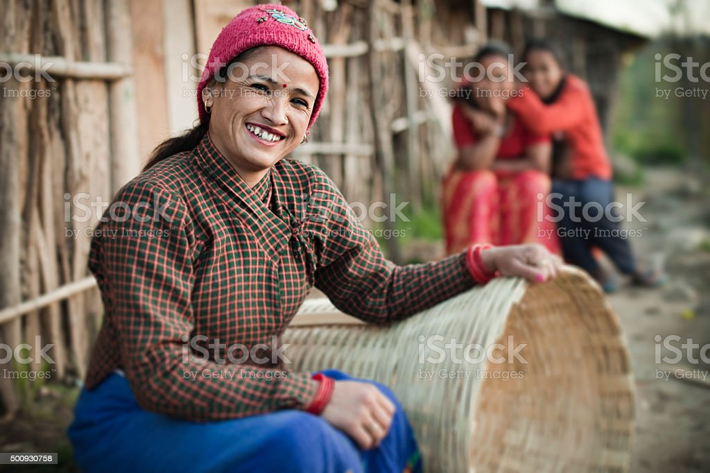 Happy rural Asian woman looking at camera, sitting near hut. stock photo