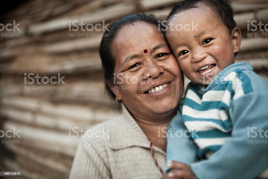 Happy rural mature Asian woman with grandson giving toothy smile. stock photo