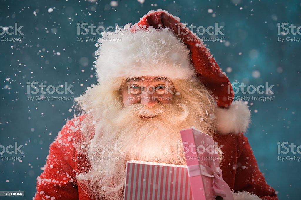 Happy Santa Claus opening his Christmas gift at North Pole stock photo