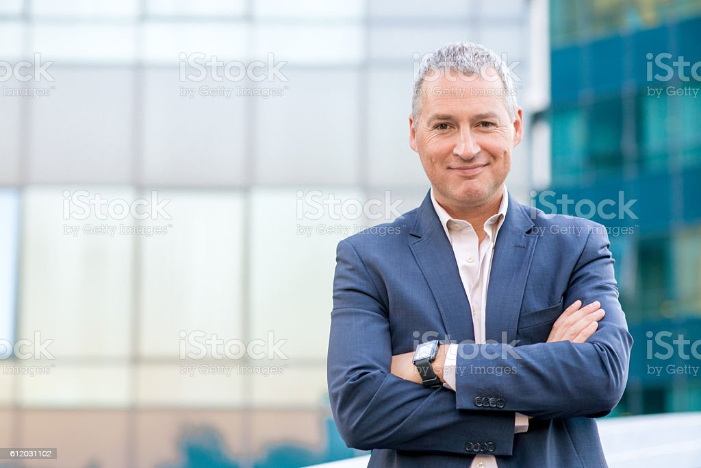 Happy satisfied mature businessman looking at camera stock photo