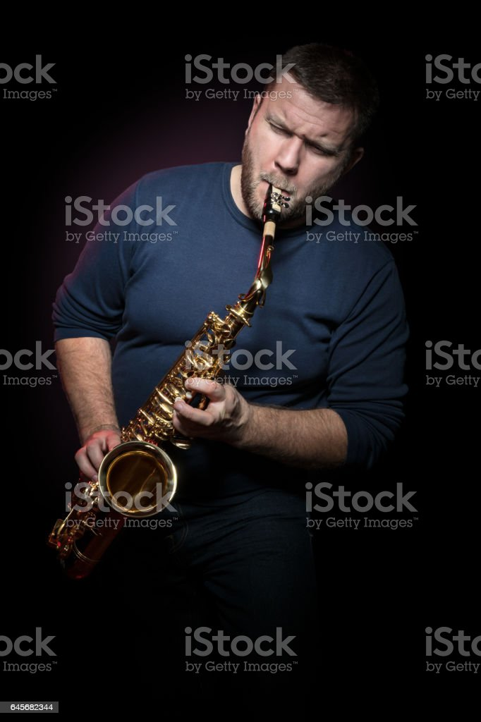 Happy saxophonist plays music on sax stock photo