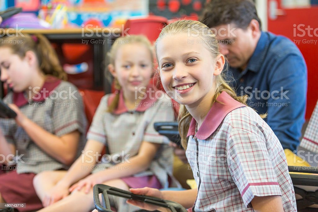 Happy School Girl Using Tablet Computer In The Classroom stock photo