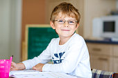 Happy school kid boy with glasses at home making homework