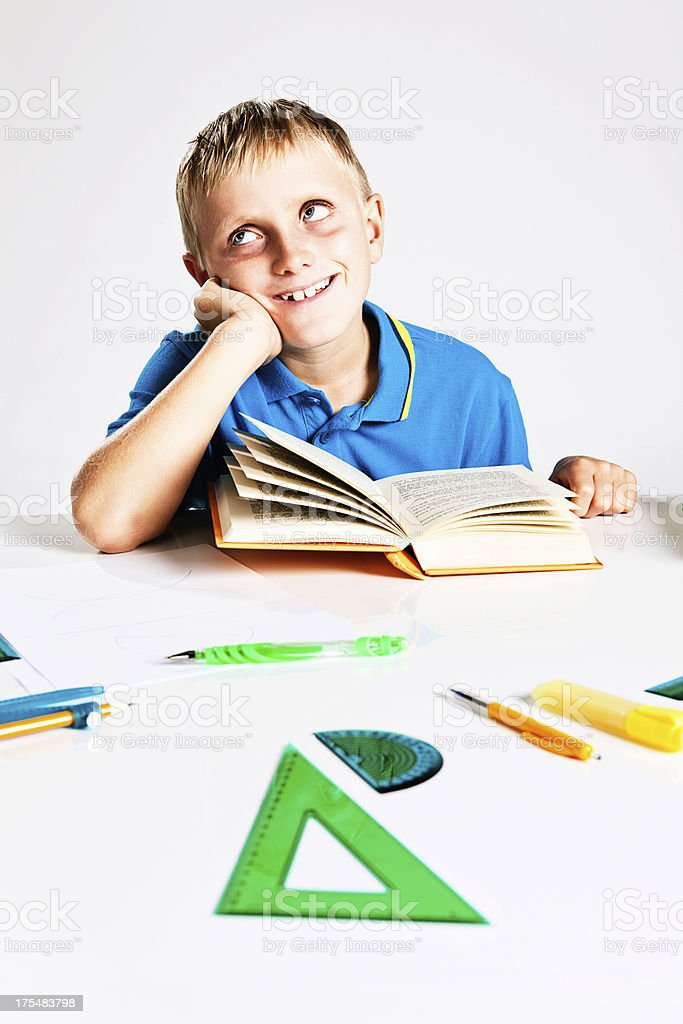 Happy schoolboy studying looks to side and smiles stock photo