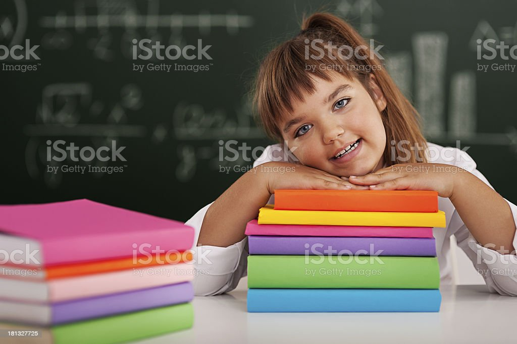 Happy schoolgirl leaning on her books royalty-free stock photo