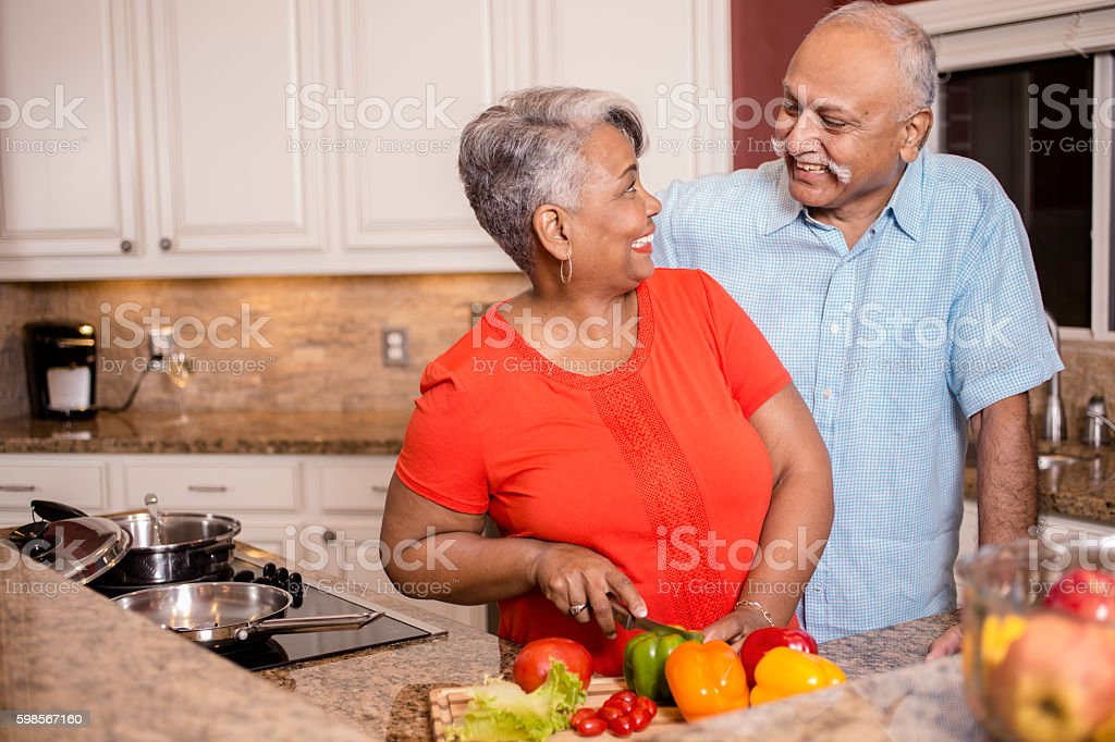Happy senior adult couple cooking together in home kitchen. stock photo