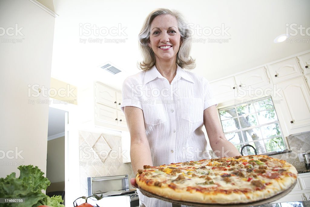 Happy Senior Adult Female Offering Out a Delicious Pizza royalty-free stock photo