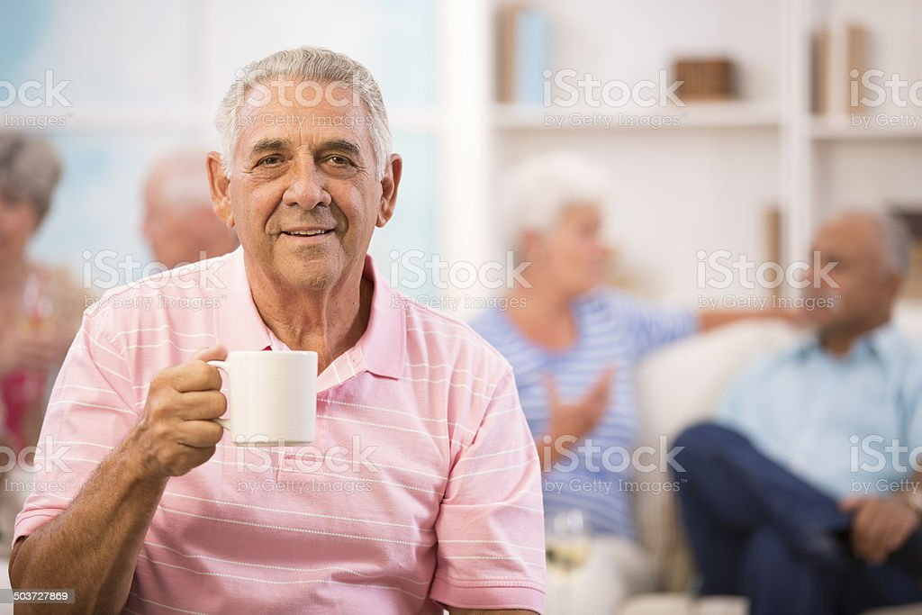 Happy, senior adult man drinks coffee. Home setting. Friends background. stock photo
