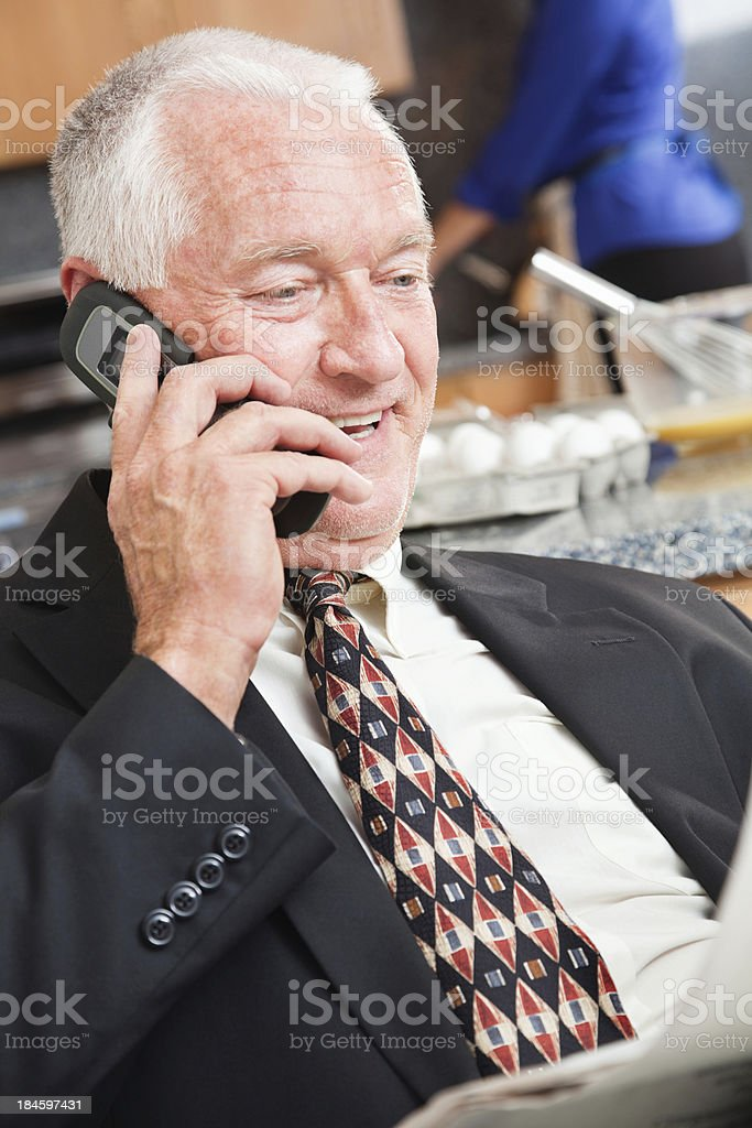 Happy senior adult man on the phone while reading newspaper royalty-free stock photo