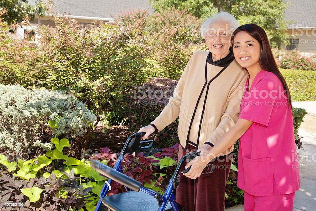 Happy Senior Adult Using Walker With Healthcare Professional royalty-free stock photo