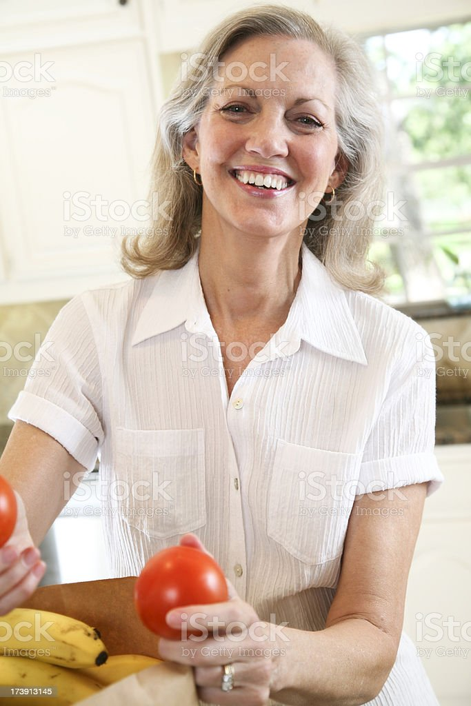 Happy Senior Adult Woman Sorting Out Her Vegetables in Kitchen royalty-free stock photo