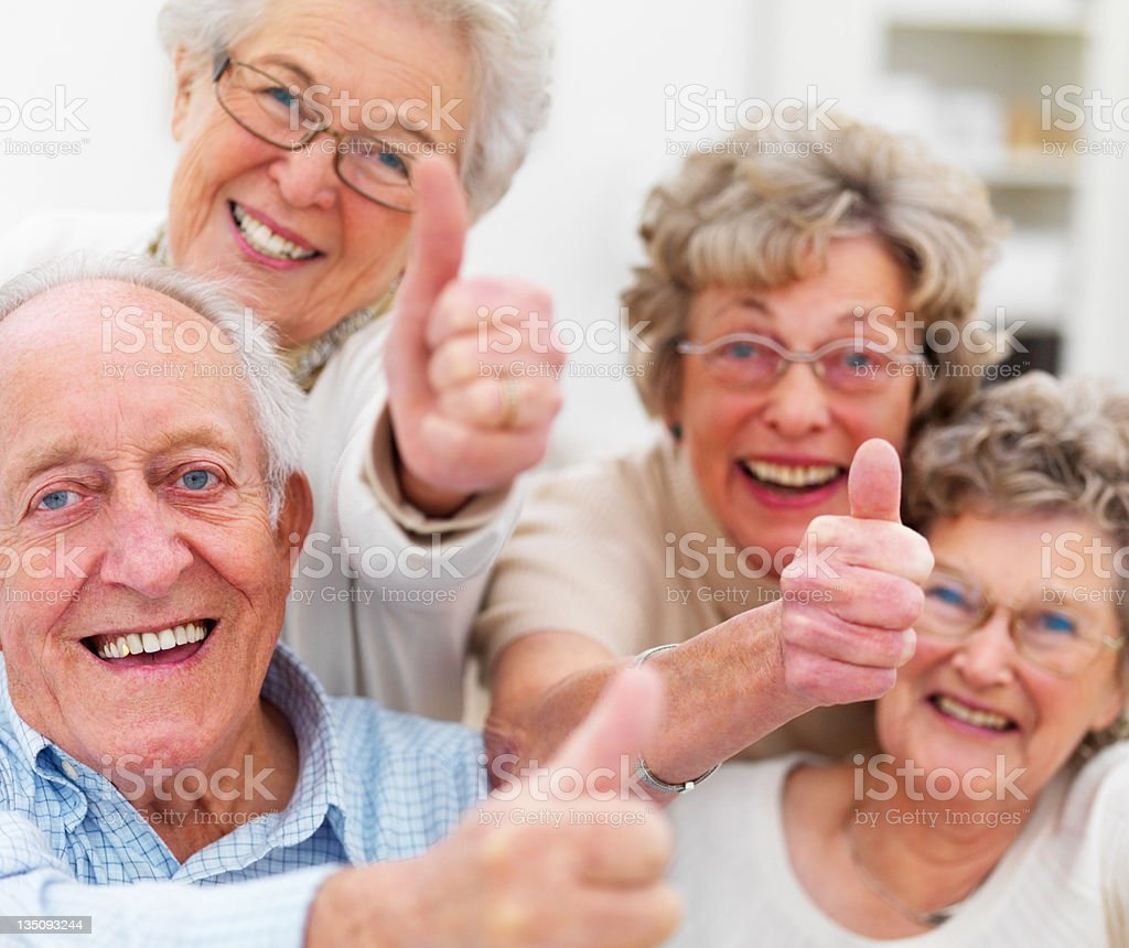 Happy senior adults showing thumbs up sign stock photo