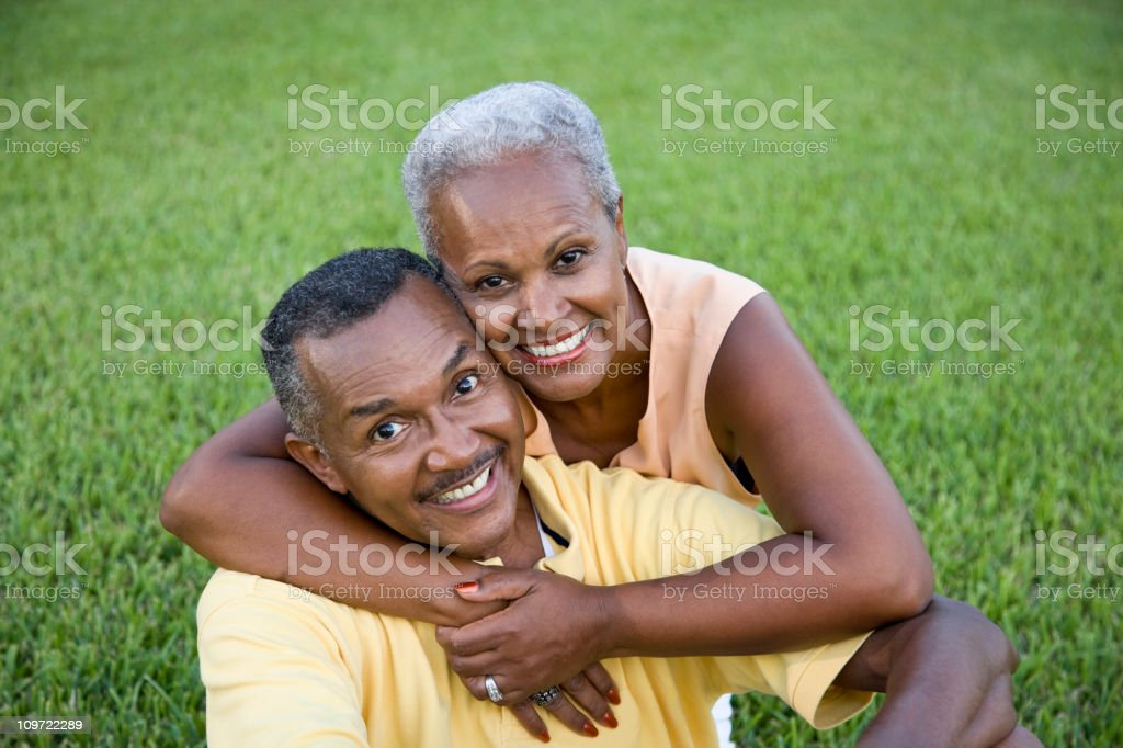 Happy senior African American couple sitting on grass together stock photo