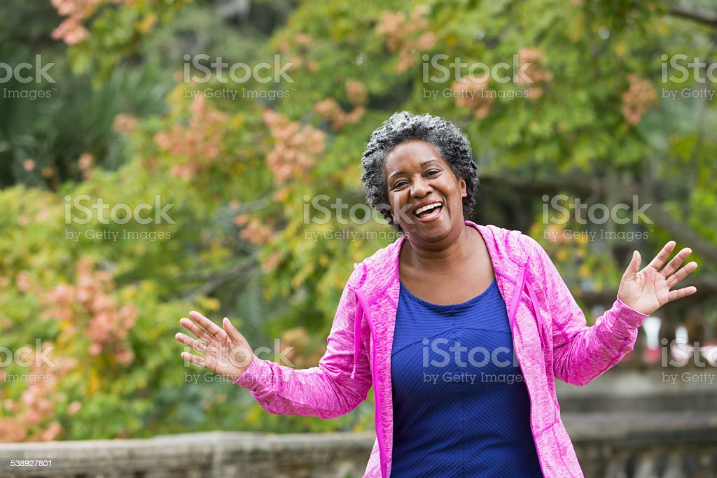 Happy senior African American woman with hands raised stock photo