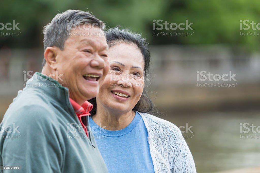 Happy senior Asian couple outdoors stock photo