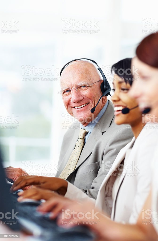 Happy senior business man with headset in a call centre royalty-free stock photo