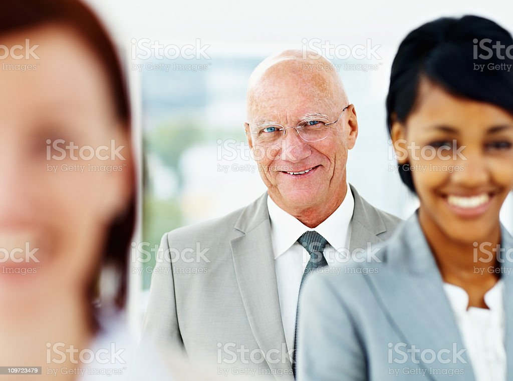 Happy senior business man with his blur team in front royalty-free stock photo