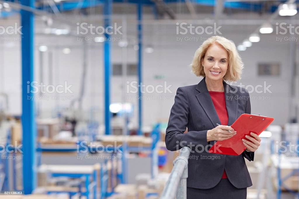 Happy senior businesswoman working in warehouse stock photo