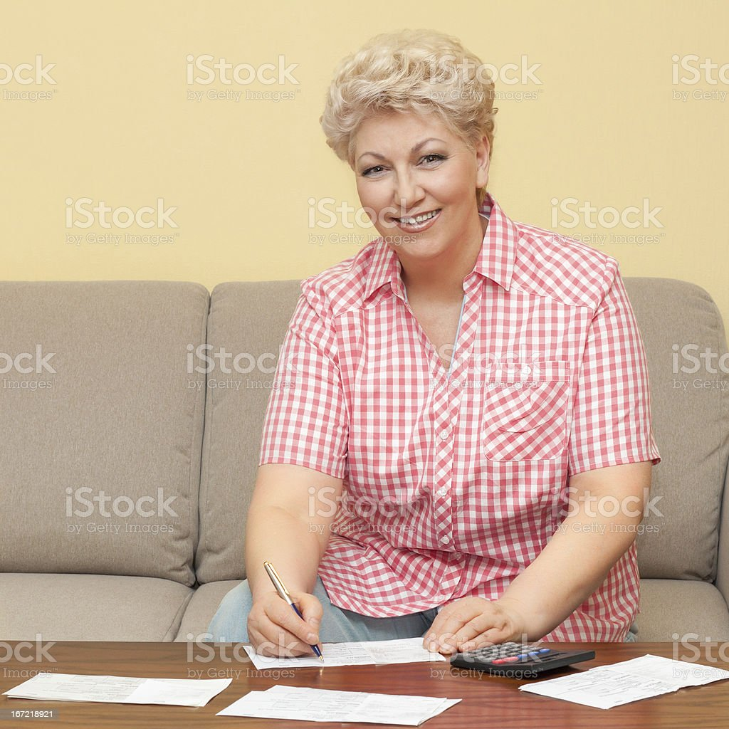 happy senior calculating her debts royalty-free stock photo