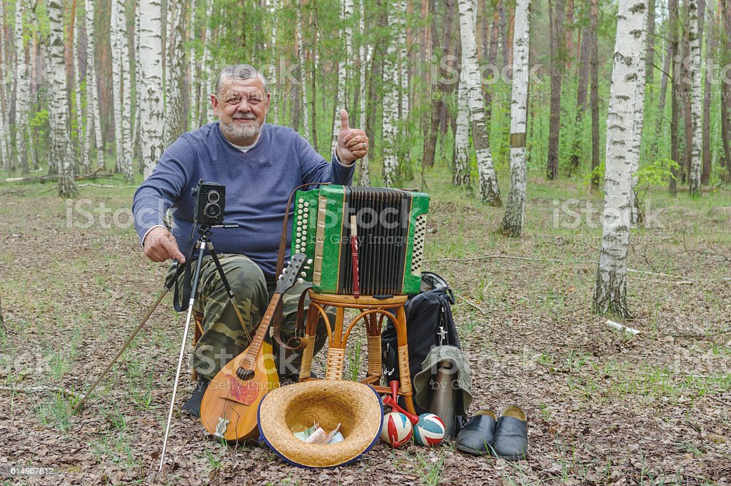 Happy senior camper is having rest in birch forest stock photo