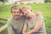 Happy senior caucasian couple hugging - outdoors portrait