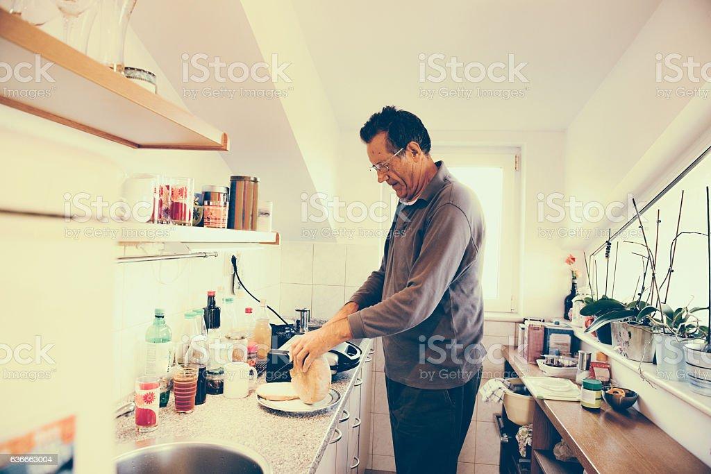 Happy Senior Caucasian Man in Pajamas Preparing Breakfast, Brac, Croatia stock photo