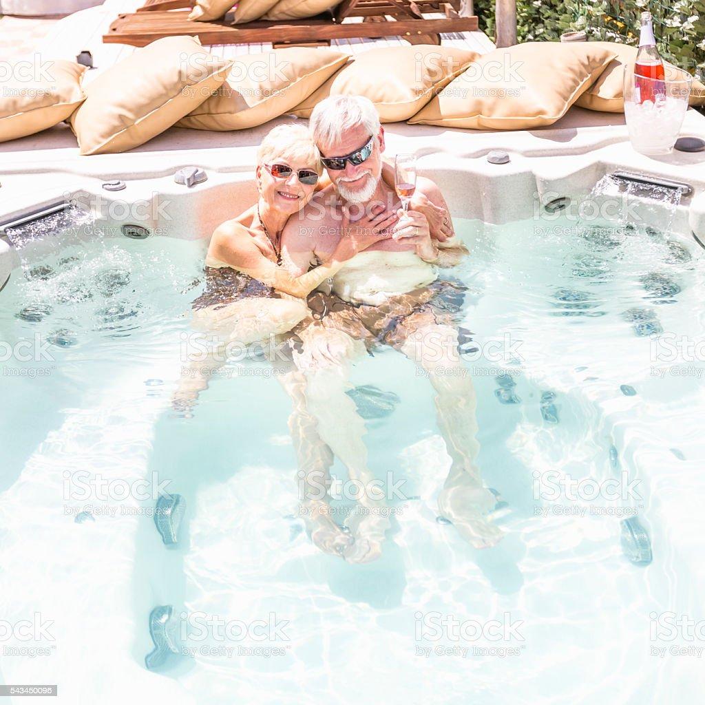 Happy senior couple are enjoying jacuzzi stock photo