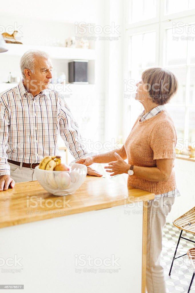 Happy senior couple at kitchen royalty-free stock photo