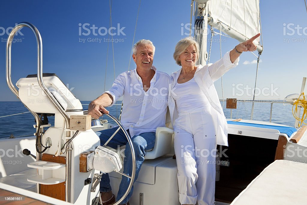 Happy Senior Couple At The Wheel of a Sail Boat royalty-free stock photo