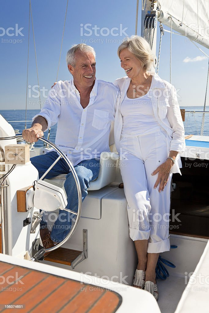 Happy Senior Couple At The Wheel of a Sail Boat stock photo