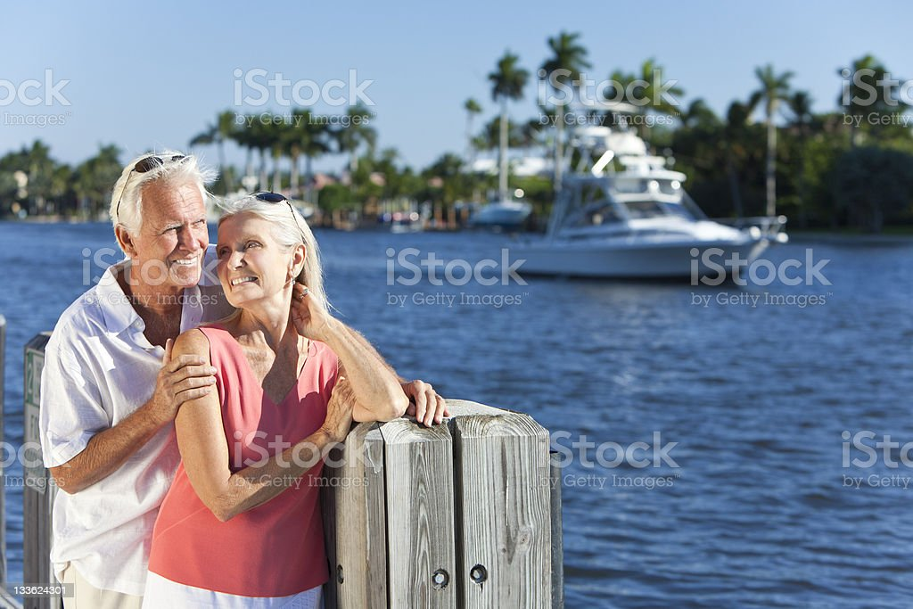 Happy Senior Couple By River or Sea with Boat stock photo