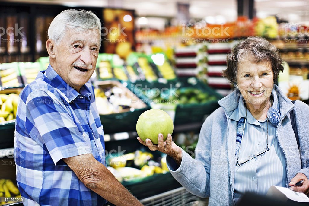 Happy senior couple choose grapefruit in supermarket stock photo