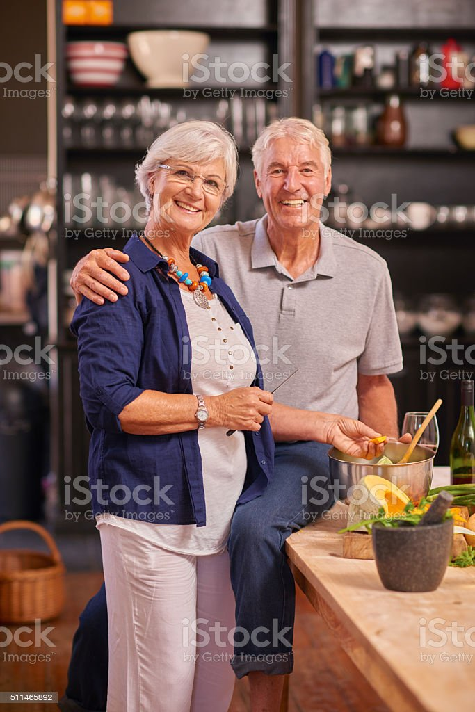 Happy senior couple cooking together at home stock photo