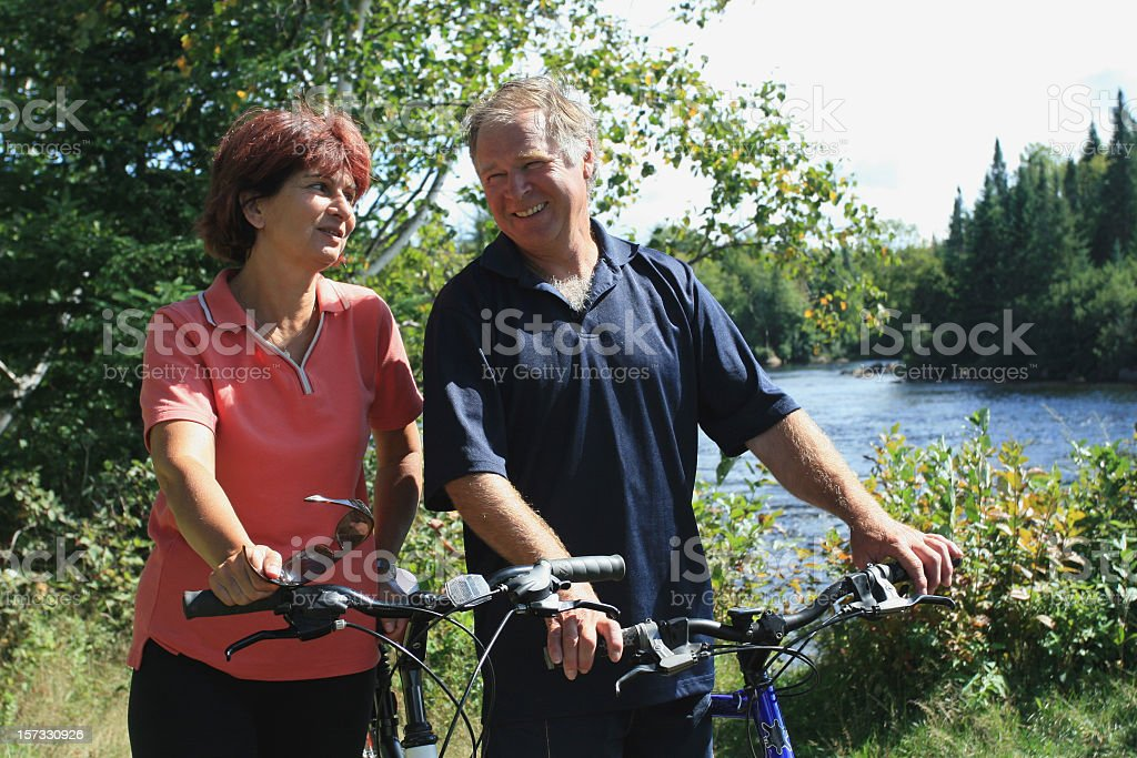 Happy Senior Couple Cycling in Forest in Summer royalty-free stock photo