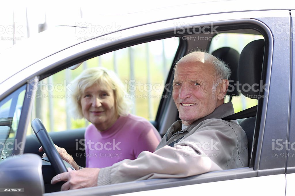 Happy senior couple driving modern car stock photo